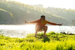 Bearded man is training on the balance board. And having fun on a green meadow next to river in the rays of summer sun. Back light, front view Royalty Free Stock Image