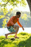 Bearded man is training on the balance board. And having fun on a green meadow next to river on sunny evening. Back light Royalty Free Stock Photo