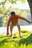 Bearded man is training on the balance board. And having fun on a green meadow next to river on sunny evening. Back light, front view Stock Images