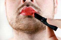 Bearded Man Transvestite Makes Up Lips with Lipstick royalty free stock images