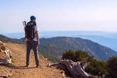 Bearded man, traveler with backpack on the mountain trail. Bearded man, traveler with backpack stands on the mountain trail and admiring the beautiful views stock photo