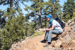 Bearded man, traveler relaxes during journey. Bearded man, traveler sits on the mountain trail - relaxes during a journey. Sunny day on Troodos, Cyprus royalty free stock photography