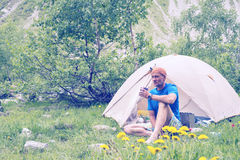 Bearded man traveler is resting next to a tent royalty free stock photo