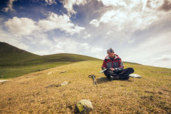 Bearded man traveler sits in mountains and studies a map Royalty Free Stock Image