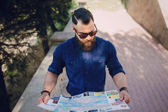 Bearded man travels with map Stock Images