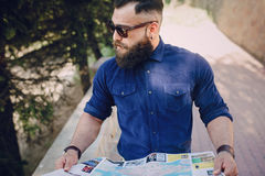 Bearded man travels with map Royalty Free Stock Images