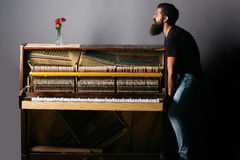 Bearded man trying to move wooden piano with rose Royalty Free Stock Photo