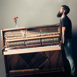 Bearded man trying to move wooden piano with rose. Handsome bearded strong man with stylish hair mustache and beard trying to move old wooden or wood open piano Stock Images