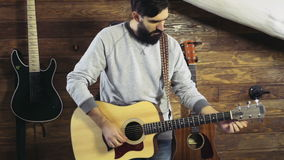 Bearded man tuning an acoustic guitar slow motion. Bearded man tuning an acoustic guitar stock footage