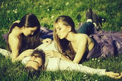 Bearded man and two women on grass. Bearded handsome men in white shirt lying with two young pretty women in violet dresses on green grass sunny day outdoor Royalty Free Stock Photography
