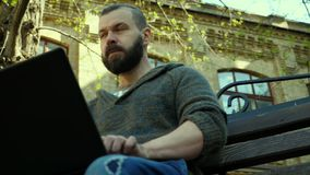 The bearded man typing on a laptop outside on a bench stock video