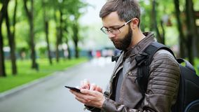 Bearded man uses mobile phone in the park. Surf the internet, playing a game, blurred people in the background stock video