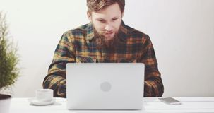Bearded Man using laptop computer, drinking coffee and talking on smartphone stock footage