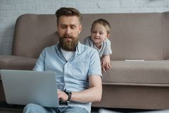 Bearded man using laptop with son near by on sofa. At home royalty free stock images