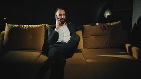 A success and happy bearded businessman is talking on the mobile phone late at home. 4K footage stock video