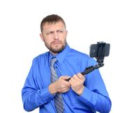 Bearded man using a selfie stick shot in studio. Isolated on white background stock photography