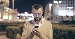 Bearded man using smart phone outdoors. Handsome young casual man using mobile cell phone smiling happy. Urban male hipster. 4K footage stock footage