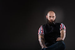 The bearded man in a vest and checkered shirt Royalty Free Stock Image