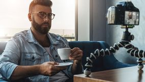 Bearded man video blogger in stylish glasses shoots video streaming for users while sitting in cafe and drinking coffee. stock photo