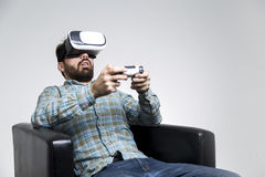Bearded man in vr glasses with controller. Portrait of a bearded man in jeans and a checkered shirt who is wearing virtual reality glasses and playing a royalty free stock photo