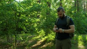 A bearded man walks through the forest and looks for a way with the navigator. GPS. Traveling stock video