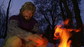 Bearded man warming his hands by the fire in winter. Tourist man evening campfire.
