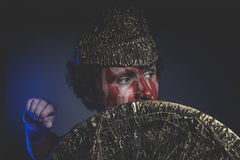 Bearded man warrior with metal helmet and shield, wild Viking Stock Photos