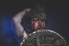 Bearded man warrior with metal helmet and shield, wild Viking Stock Image