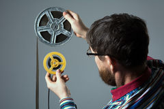 Bearded man watch two film reel 16mm Royalty Free Stock Image
