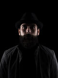Bearded man wearing black hat looking at camera. High contrast low key dark shadow portrait isolated over black background Stock Photography