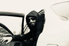 Man wearing a hood dress unique photo. A bearded man wearing black hood dress sitting in a car unique black and white photo stock photo