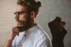 Bearded man wearing glasses touching chin stock photo