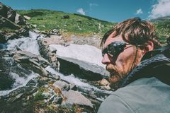 Bearded Man wearing mountain sunglasses hiking Travel Lifestyle concept adventure. Vacations survival outdoor stock photo