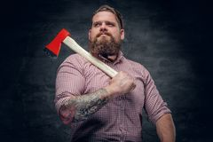 Bearded man wearing pink plaid shirt and holds an axe. Stylish bearded male with tattoos on arms wearing pink plaid shirt and holds an axe Royalty Free Stock Image