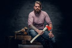 Bearded man wearing pink plaid shirt and holds an axe. Stylish bearded male with tattoos on arms wearing pink plaid shirt and holds an axe Stock Photos