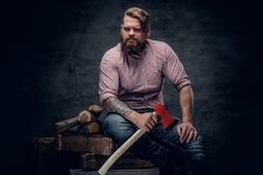 Bearded man wearing pink plaid shirt and holds an axe. Stylish bearded male with tattoos on arms wearing pink plaid shirt and holds an axe Royalty Free Stock Photography