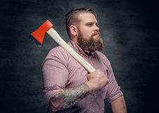 Bearded man wearing pink plaid shirt and holds an axe. Stylish bearded male with tattoos on arms wearing pink plaid shirt and holds an axe Royalty Free Stock Photo