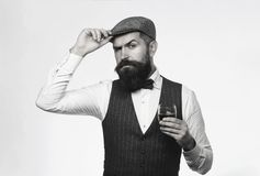 Bearded man wearing suit and drinking whiskey, brandy, cognac. Bearded and glass of whiskey. Sommelier tastes expensive stock photos