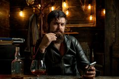 Bearded man wearing suit and drinking whiskey brandy or cognac. Sommelier tastes alcohol drink. Degustation and tasting. Man drinks brandy or whiskey. Bearded Stock Photos