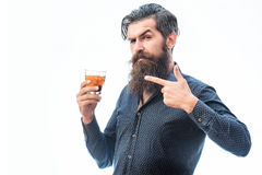 Bearded man with whiskey. Handsome bearded man with stylish hair mustache and long beard on serious face in blue fashion shirt holding glass of whiskey and shows stock photography