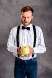 Bearded man in white shirt and bow tie looking at piggy bank. Young bearded man in white shirt and bow tie looking at piggy bank stock image