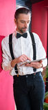 Bearded man in white shirt with bow-tie with tablet PC Royalty Free Stock Image