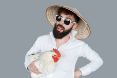 Bearded man in white shirt holding a chicken royalty free stock photo