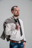 Bearded man in a white shirt holding a jacket in h. Portrait of a bearded man in a white shirt holding a jacket in his hand behind his back and looking away Royalty Free Stock Photo