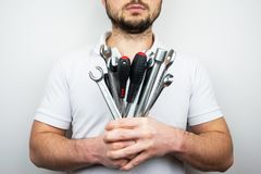A bearded man in a white T-shirt with a bouquet of wrenches and screwdrivers.  royalty free stock photo