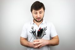 A bearded man in a white t-shirt looks surprised at a bouquet of wrenches and screwdrivers.  stock photo