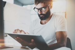 Bearded man in white tshirt working with portable electronic pro tablet computer at modern lightful office.Horizontal Royalty Free Stock Image