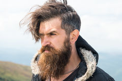 Bearded man on windy mountain top on natural cloudy sky. Bearded man, long beard, brutal caucasian hipster with moustache, unshaven guy with stylish hair getting stock photography