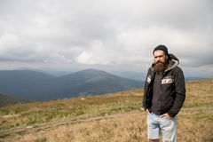 Bearded man on windy mountain top on natural cloudy sky. Bearded man, long beard, brutal caucasian hipster with moustache, unshaven guy in jacket with stylish stock image