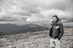 Bearded man on windy mountain top on natural cloudy sky Stock Photography